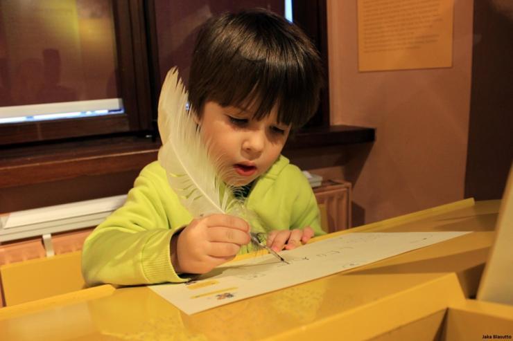Otrok piše pismo v Muzeju pošte in telekomunikacij.