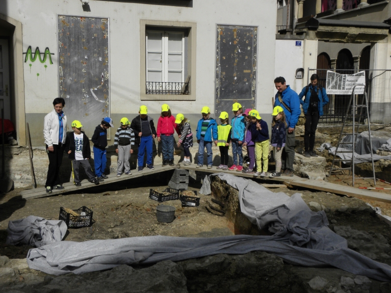 Šolarji med ogledom arheoloških izkopavanj. (©ZVKDS, 2014)
