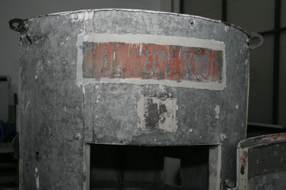 Detajl zgornjega dela stolpa, kjer so vidne sledi prvotnega napisa (ZVKDS RC – V. Benedik).